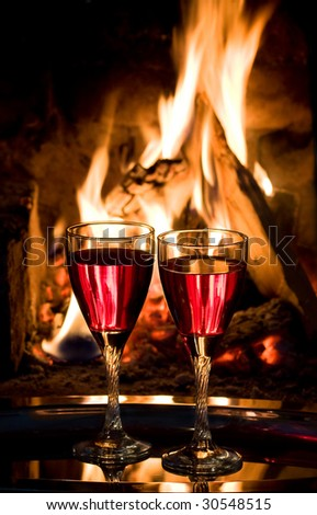 glasses with red wine at a fire in the fireplace - stock photo