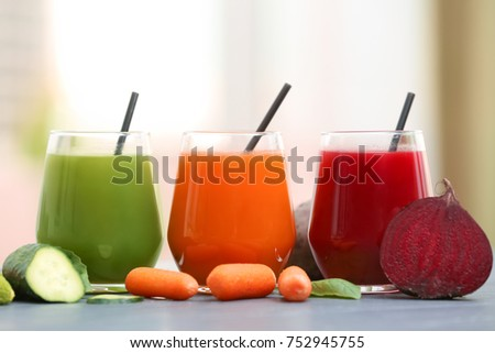 Glasses with various fresh juices and ingredients on table