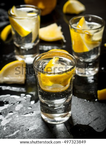 Glasses with vodka and lemon. On a black wooden background.