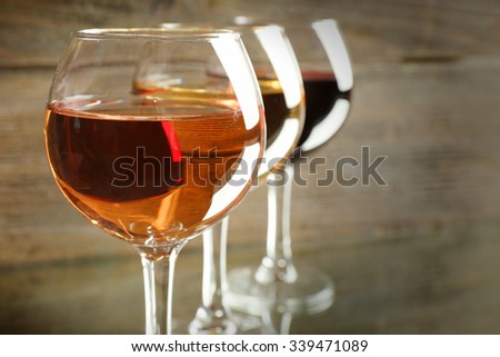 Glasses with white, rose and red wine on wooden background, close up - stock photo