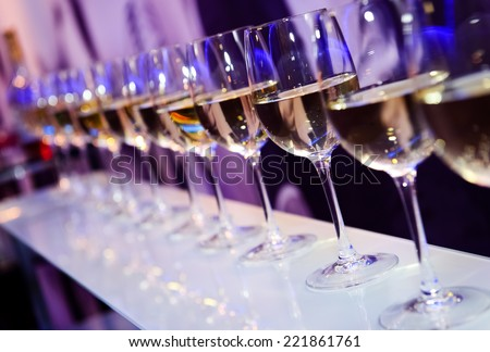 Glasses with white wine lit by festive lights on dark-purple background - stock photo