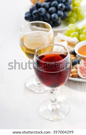 glasses with wine and snacks on white table, vertical - stock photo