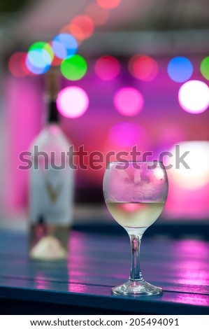 Glasses with wine on the table in the light of lanterns of night club. - stock photo