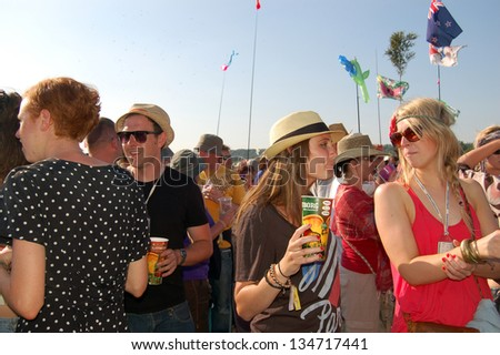 GLASTONBURY,UK - JUNE, 26: A group of festival goers enjoy a cold drink amongst a crowd at Glastonbury Festival on June 26th, 2010 at Pilton Farm in Somerset. - stock photo