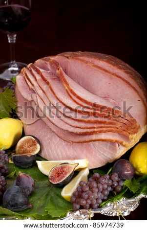 Glazed delicious whole baked honey sliced ham with figs, lemons and champagne grapes. - stock photo