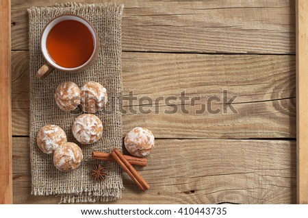 Glazed gingerbread, tea cup and old wooden table background. Top view - stock photo