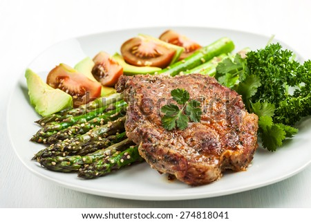 Glazed green asparagus with sesame seeds and grilled pork chop - stock photo