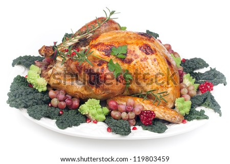 Glazed roasted turkey garnished with grapes, pomegranates, and broccoli over white background - stock photo