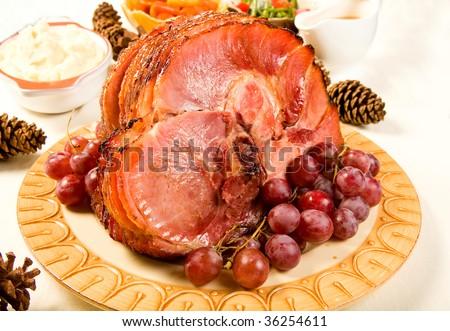 Glazed Spiral Sliced Ham garnished with red globe grapes - stock photo