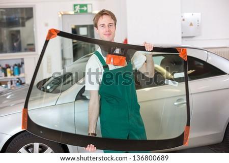 Glazier handling car windshield or windscreen made of glass in garage - stock photo