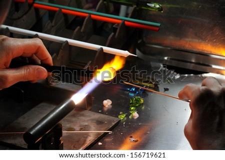 Glazier with gas torch lit while blending and shaping glass