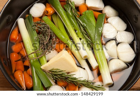 glazing vegetables cooking carrots leeks and onions with thyme and rosemary and butter. classic french cooking  - stock photo