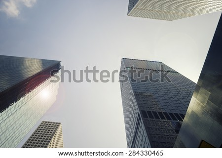 Gleaming glass generic anonymous skyscraper towers hosting global power houses of commerce law and financial business. - stock photo
