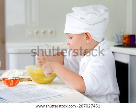 Gleeful young chef baking in the kitchen in his white toque and uniform looking with anticipation at the batter mixture he is whipping up in a mixing bowl - stock photo