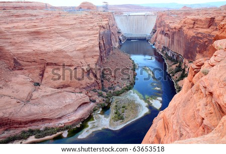 Glen canyon dam harnesses electricity from the Colorado River and forms the border of Lake Powell.  Tall, sheer, orange colored canyon walls tower over the river, forming great viewpoints - stock photo