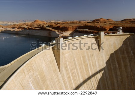 Glen Canyon Dam in Page, Arizona lit by morning sun with cars parked on the road running along its' top. - stock photo