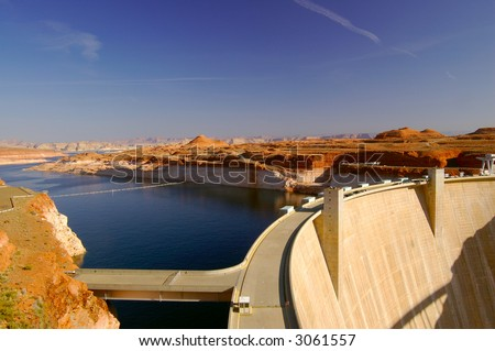 Glen Canyon Dam in Page, Arizona lit by morning sun with cars parked on the road running along its' top.