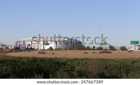 GLENDALE, AZ - JANUARY 24, 2015: Undeveloped city area lot contrasting University of Phoenix Cardinal Stadium that hosts Super Bowl XLIX in Glendale, Phoenix metro, AZ - stock photo