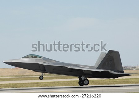 """GLENDALE, AZ - MARCH 21: A U.S. Air Force F-22 Raptor lands on the runway at the biennial air show (""""Thunder in the Desert"""") at Luke Air Force Base on March 21, 2009 in Glendale, AZ. - stock photo"""