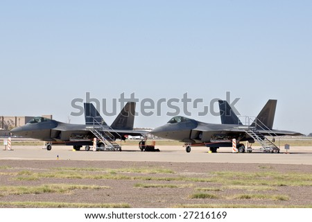 """GLENDALE, AZ - MARCH 21: Two U.S. Air Force F-22 Raptor fighters parked on the runway at the biennial air show (""""Thunder in the Desert"""") at Luke Air Force Base on March 21, 2009 in Glendale, AZ. - stock photo"""