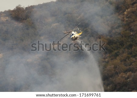 GLENDORA, CALIFORNIA, USA - JANUARY 16, 2014: A large wildfire burns out of control in the hills above Glendora. Firefighters, helicopters and aircraft from many jurisdictions work to control it .