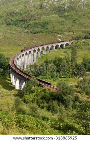 Glenfinnan Viaduct, Lochaber, Highlands, Scotland with the Jacobite steam train passing over. Completed in 1901 as part of the West Highland Line it is the longest concrete railway bridge in Scotland. - stock photo