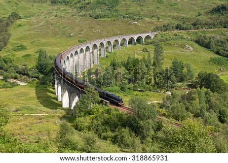 Glenfinnan Viaduct, Lochaber, Highlands, Scotland with the Jacobite steam train passing over. Completed in 1901 as part of the West Highland Line it is the longest concrete railway bridge in Scotland.