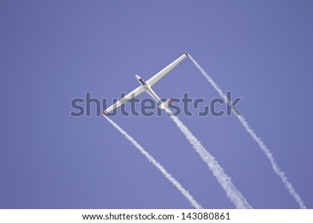 Glider performing aerobatics with smoke trails at airshow. - stock photo