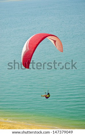 gliderman suspended under the glider on the sky - stock photo