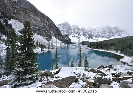 Glimmering crystal sapphire blue of Moraine Lake framed with ten snow peaks standing white-gray in morning fog Banff