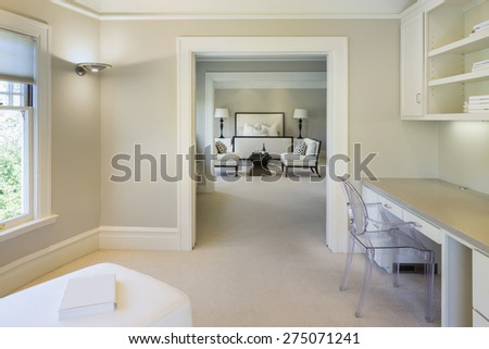 Glimpse from home office into classical luxurious beige / white bedroom interior in mansion with double chair, luxurious bed and fitted shelves.  - stock photo