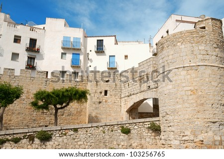 Glimpse of Peniscola and part of its fortified walls with town gate - stock photo