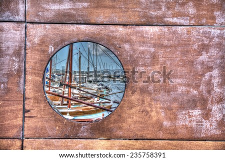 glimpse of the port through a porthole. Processed for hdr tone mapping effect. - stock photo