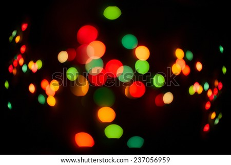 Glitter multicolored festive lights. Color defocused texture on black background