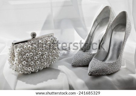 glitter silver shoes and clutch bag on white - stock photo