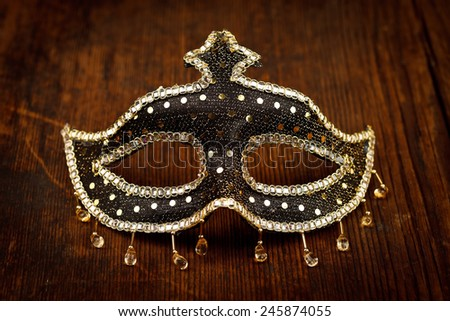 Glittering carnival mask on rustic wooden table - stock photo