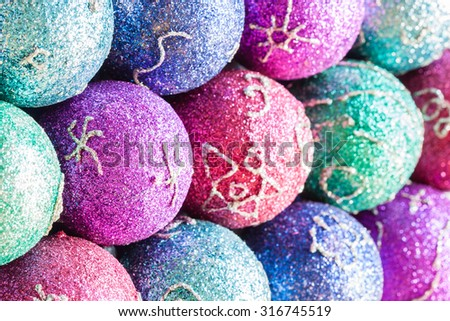 Glittering Christmas ornaments - Christmas ornaments with colorful glitter and simple festive artwork. Shallow Depth of field used for background. - stock photo