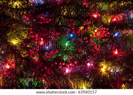 Glittering LED Christmas Lights on a Christmas Tree with Holly and Ornament Decorations - stock photo