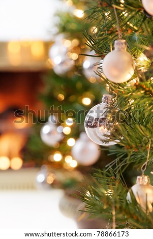 Glittering silver and white Christmas tree decorations by a warm fire - stock photo