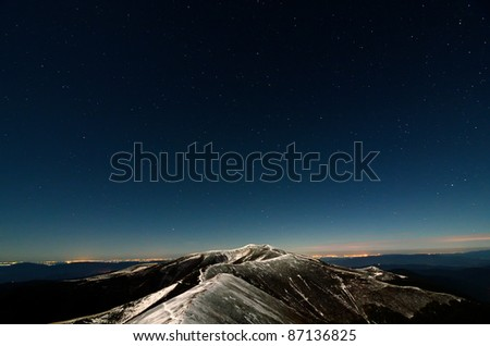 Glittering stars above snowy autumn mountain ridges and city lights - stock photo