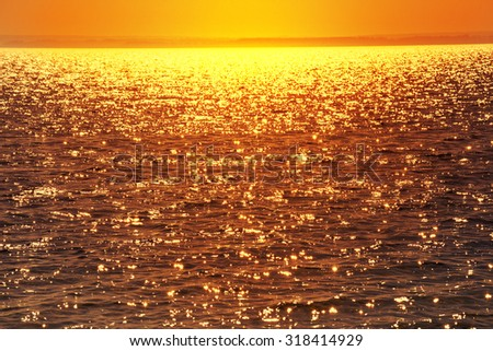 Glittering water at sunset. Sea water background. - stock photo