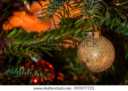 Glittering Xmas bauble in gold hanging on a tree - stock photo