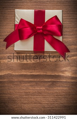 Glittery gold giftbox on vintage wooden board copy space. - stock photo