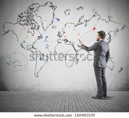Global business concept with businessman that draws a world map - stock photo