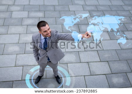 global business, development, technology and people and concept - young smiling businessman pointing finger to world map projection outdoors from top - stock photo