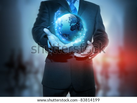 Global Communication - A businessman holding a glowing, connected, World.