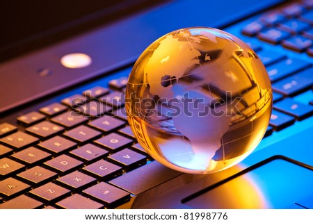 global computer business concept with small globe on laptop keyboard in mixed light - stock photo