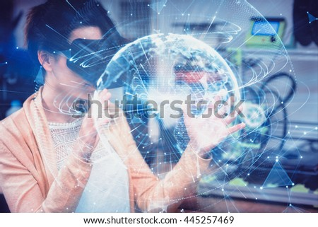 Global technology background in blue against female graphic designer using the virtual reality headset - stock photo