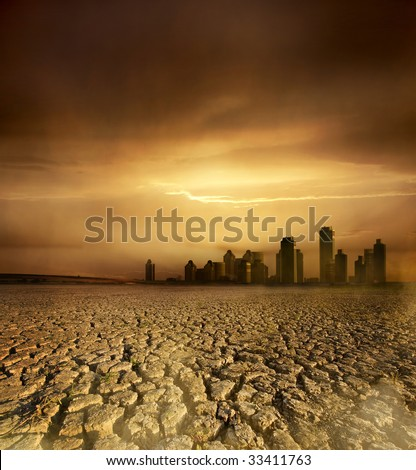 Global Warming and pollution theme with cracked land and the cityscape - stock photo