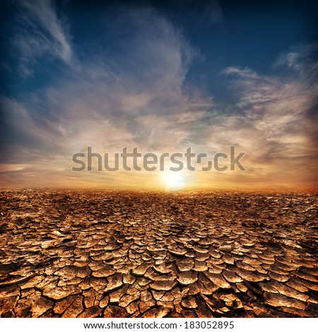 Global warming concept. Lonely drought cracked desert landscape under evening sunset sky - stock photo